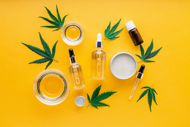 Cbd oil, hemp tincture, cannabis cosmetic product for skin care with cannabinoid. alternative medicine, pharmaceutical medical cannabis. varieties of hemp oil, serum butter on yellow background.