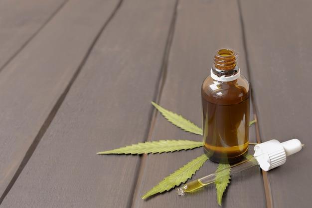 복사 공간이 있는 나무 배경에 마리화나 녹색 잎이 있는 유리 병에 든 도심 오일