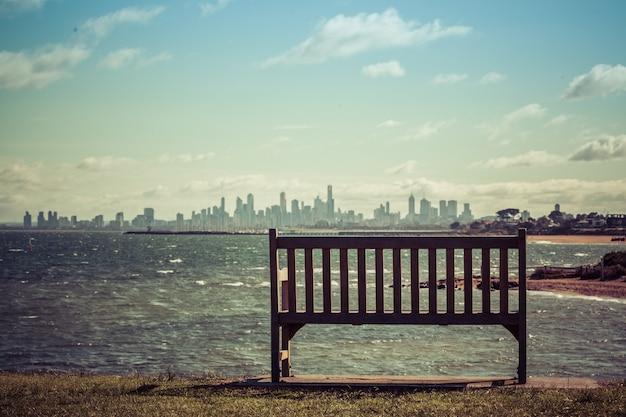明るい晴れた日にメルボルンcbdのスカイラインを見下ろす海海岸の空の木製ベンチ