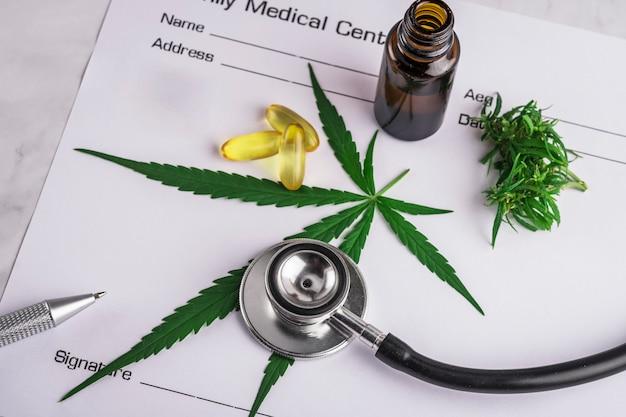 医療処方シートの上の大麻製品、ピルおよびcbdオイルの盛り合わせ