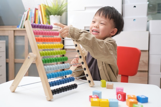 Cboy using the abacus with beads and wooden brick with numbers