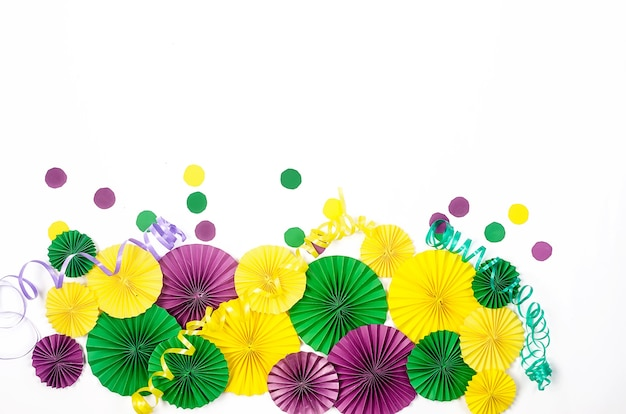 Ccolorful paper confetti, carnivale mask and colored serpentine on a yellow background