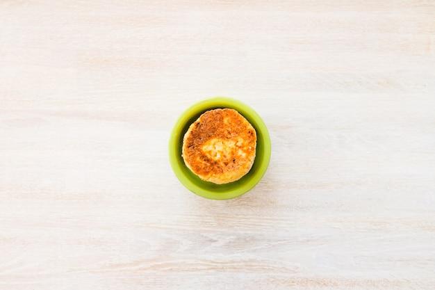 コテージチーズのパンケーキは、白い木製のテーブルの上の丸い緑のボウルにスタックします。