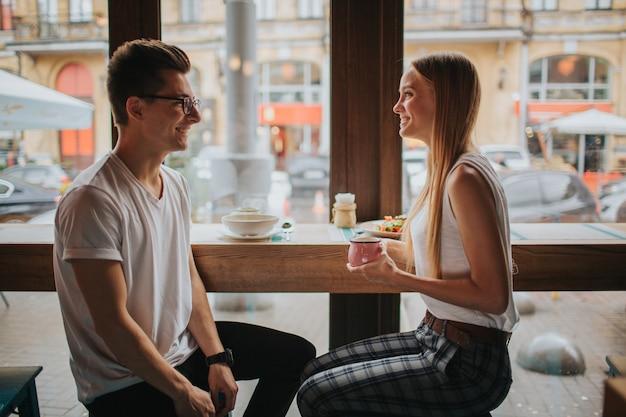 バーやレストランで素敵なデートをする幸せな若いccouple。彼らは自分自身についていくつかの話をし、お茶やコーヒーを飲み、サラダやスープを食べます