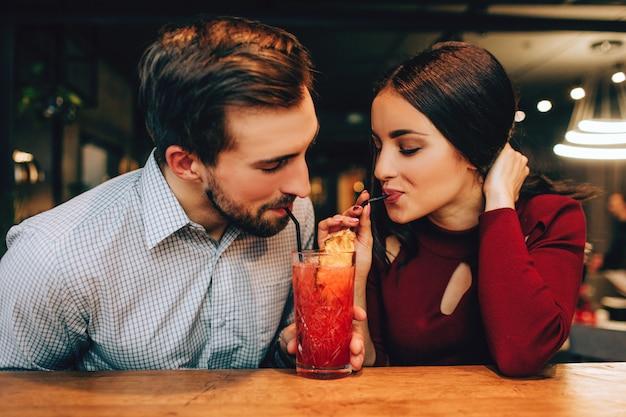 一緒に座って、同時に同じグラスから赤いカクテルを飲む若いccoupleの素敵な写真。彼らは一緒に幸せそうに見えます。