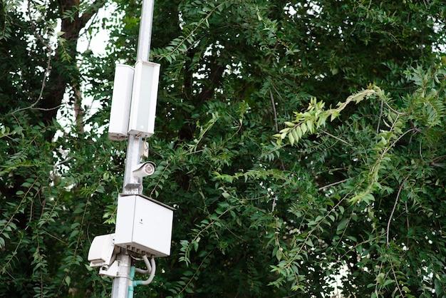 Камера видеонаблюдения и предупреждающие колонки на столбе в парке