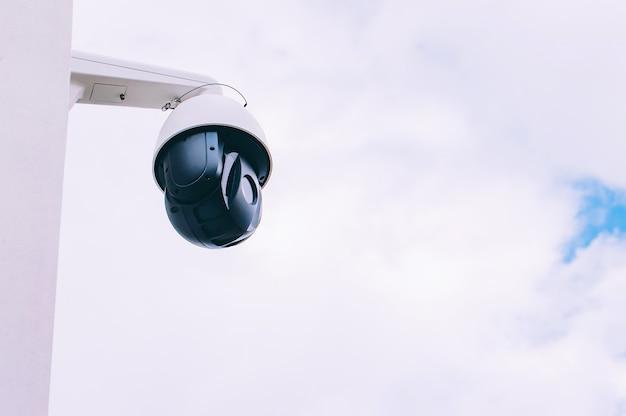 家の壁にあるcctvカメラ。空を背景に。