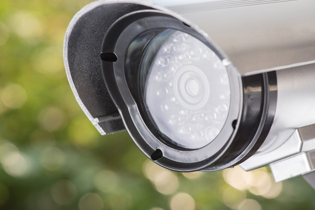 Cctv camera security ccd on green bokeh nature background