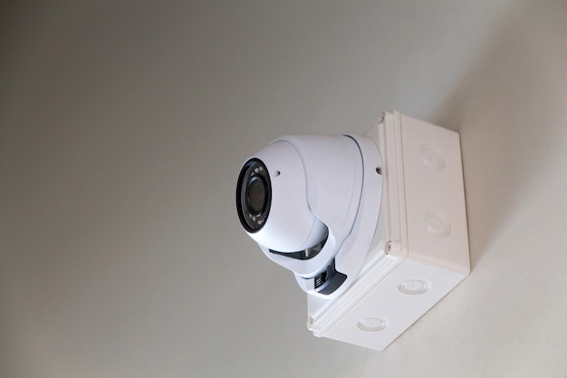 A cctv camera on wall inside the building for watches down below important events