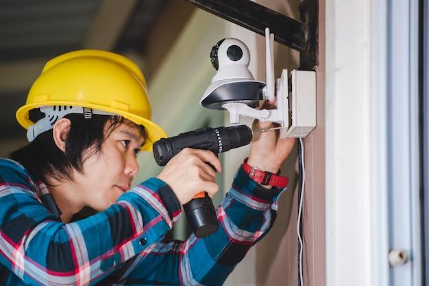 Монтаж видеонаблюдения с участием молодых азиатских техников. установка, такая как wi-fi ip-камера. концепция: беспроводная ip-камера.