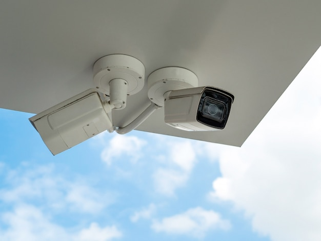 Cctv is installed under the building balcony against blue sky. cctv for security monitoring.