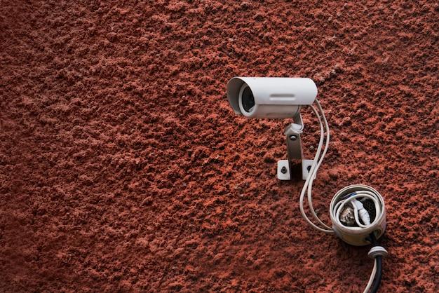 Cctvセキュリティカメラと白いワイヤーが付いている暗赤色の壁。防犯カメラ