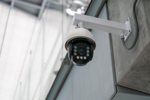 На бетонном здании установлена камера видеонаблюдения.