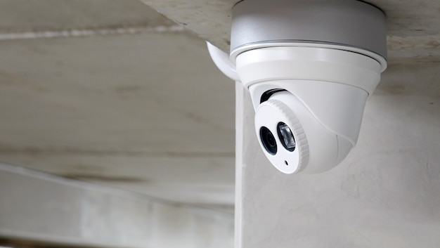 Cctv surveillance camera installed on concrete wall in the building