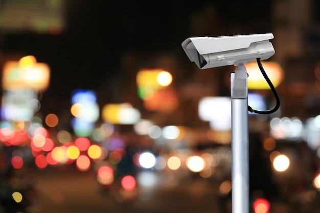 야간 배경의 흐릿한 도로에 있는 cctv 시스템과 작업에 디자인을 위한 복사 공간이 있습니다.