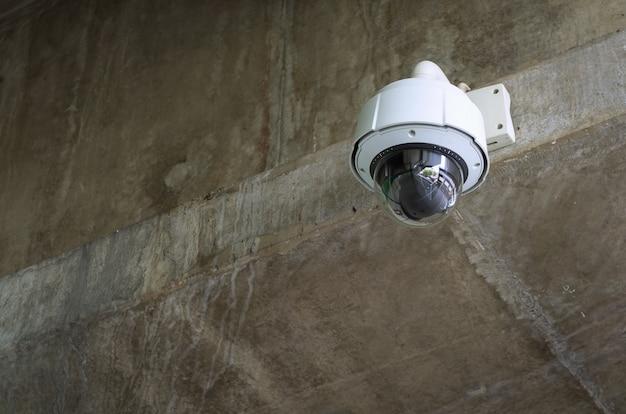 白い円形の監視カメラがセメント壁に詰まっています。 cctv。