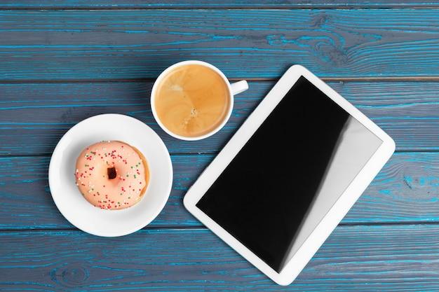 コーヒー、ドーナツ、テーブルの上のタブレットのccup
