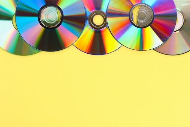 古いcd、パステル調の背景にdvdの山。テキストを追加するためのコピースペースを持つ使用済みのほこりっぽいディスク。