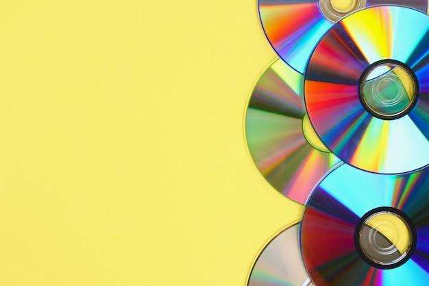 古くて汚いcdの束、パステルの背景にdvd。コピースペースのある使用済みのほこりの多いディスク