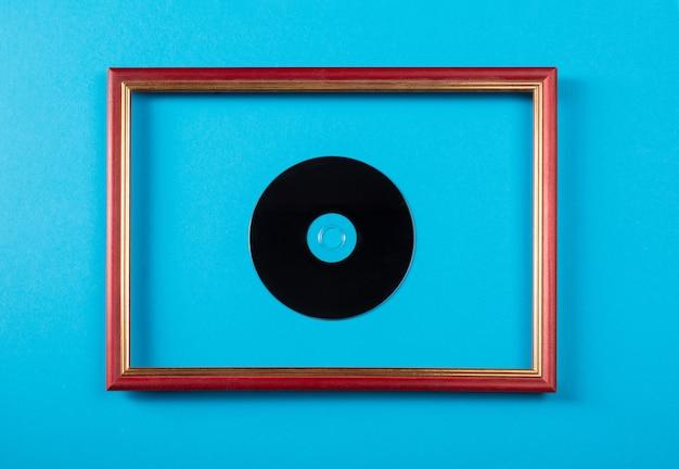 Диск в деревянной фоторамке на синей стене.
