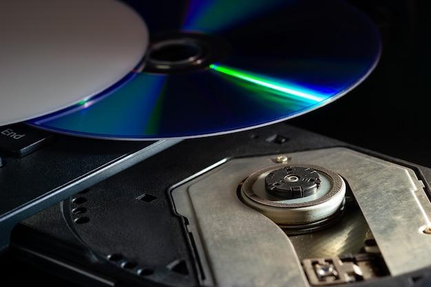 Компакт-диск на компьютере, ноутбук cd-rom в темноте. понятие технологических достижений в компьютерных системах регистрации данных.