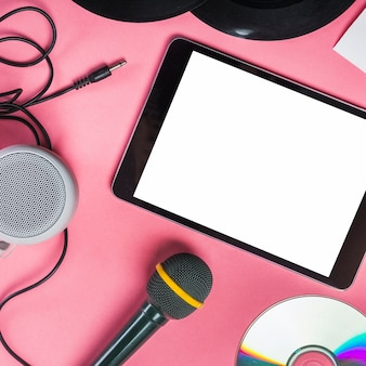 Cd; vinyl record; microphone; speaker and digital tablet on pink background