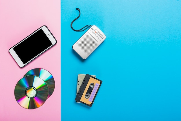 デュアルピンクとブルーの背景に携帯電話とcdをテープレコーダーとカセットに置き換えました