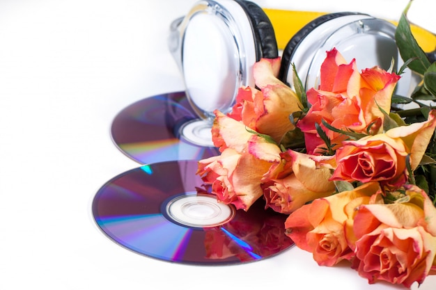 Cds, headphones and roses over white