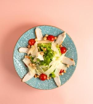 Insalata caesar con pollo alla griglia, pomodorini, lattuga parmezan e fette biscottate sul piatto