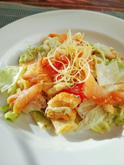 Ceasar salad with prosciutto ready-to-eat.. ceasar salad on white plate on restaurant tabletop. natural trendy hard daylight