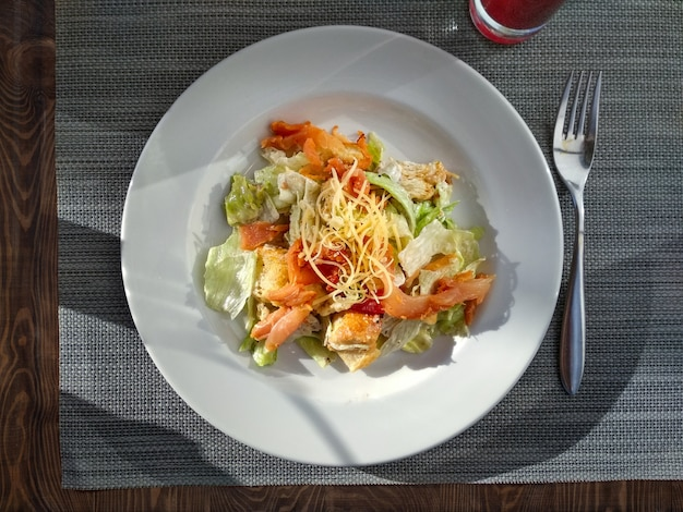 Ceasar salad with prosciutto ready-to-eat. top view. ceasar salad on white plate on restaurant tabletop. natural trendy hard daylight