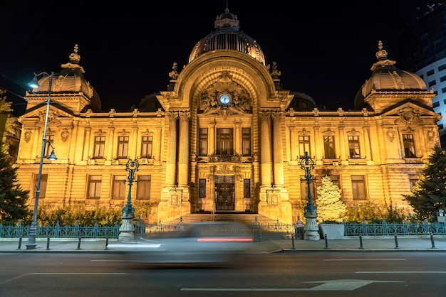 The cec palace at night and long exposure, yellow illumination, trace of moving car on the foreground in bucharest, romania