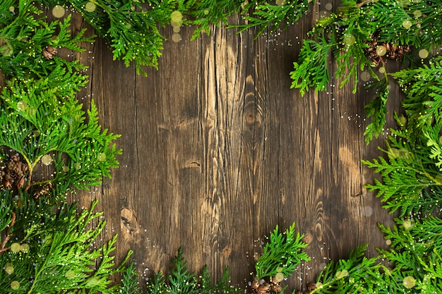 Cedar branches over wooden background