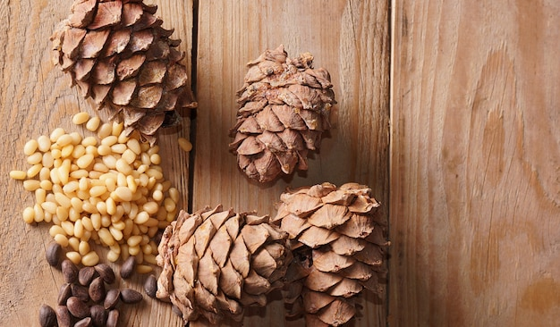 Cedar cone and pine nuts lie on a wooden table