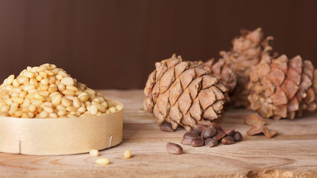 Cedar cones and pine nuts are on a wooden table.