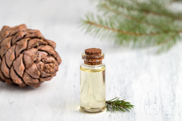 Cedar essential oil in a glass bottle. soft focus. white wooden background.