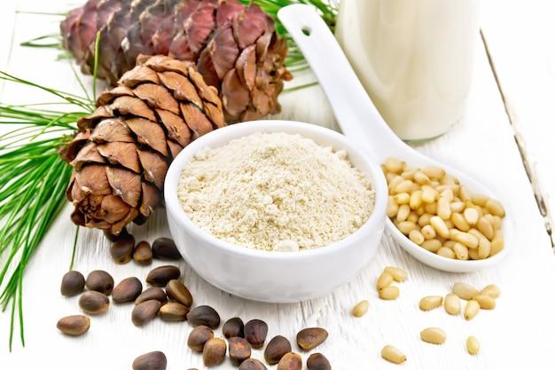 그릇에 삼나무 가루, 견과류, 콘, 껍질을 벗긴 견과류가 든 숟가락, 녹색 소나무 가지, 삼나무 우유가 밝은 나무 판자 배경에 있는 병에 들어 있습니다.