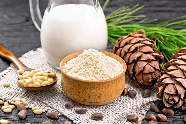 그릇에 삼나무 가루, 견과류, 원뿔 2개, 껍질을 벗긴 견과류를 삼베 위에 얹은 숟가락, 녹색 가지, 삼나무 우유는 어두운 나무 판자 배경에 있는 주전자에 있습니다.