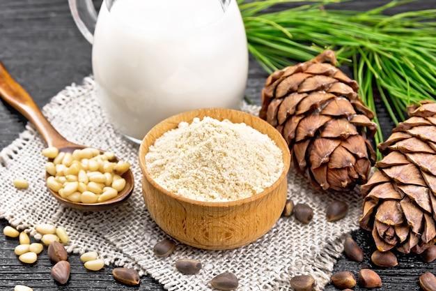 ボウルに杉粉、ナッツと2つのコーン、黄麻布に皮をむいたナッツのスプーン、緑の枝、木の板の背景に水差しに杉のミルク
