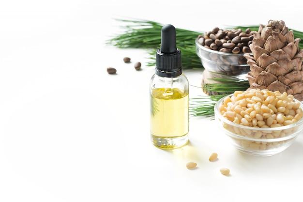 Кедровое масло, ветви и кедровая шишка на белом. копировать пространство красота и здоровая концепция.