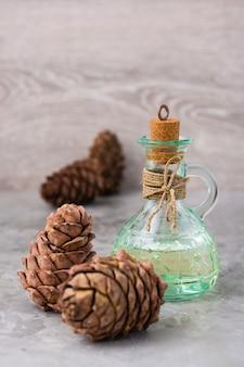 瓶の中のヒマラヤスギ油とテーブルのヒマラヤスギの円錐形。樹脂杉の処理。代替医療、自然医学