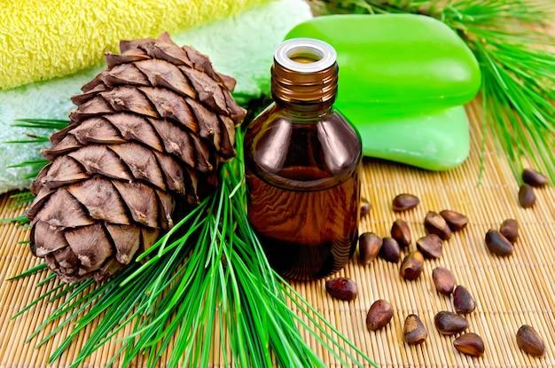 瓶の中の杉油、杉の円錐形の枝、杉の実、2つの緑色の石鹸、竹のマットの上に2つのタオル