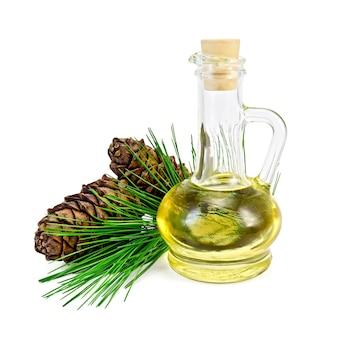 ガラス瓶の中の杉油、白い背景で隔離の2つの円錐形の杉の小枝