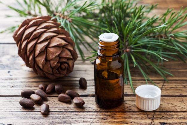 Cedar and spruce essential oil in small glass bottles on wooden table.