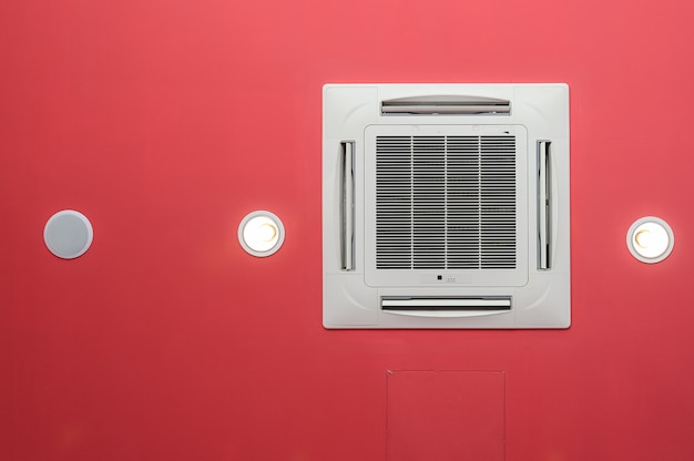 Ceiling air conditioner on red ceiling light and loudspeaker.