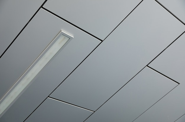 Ceiling covered with smooth white panels with a lamp