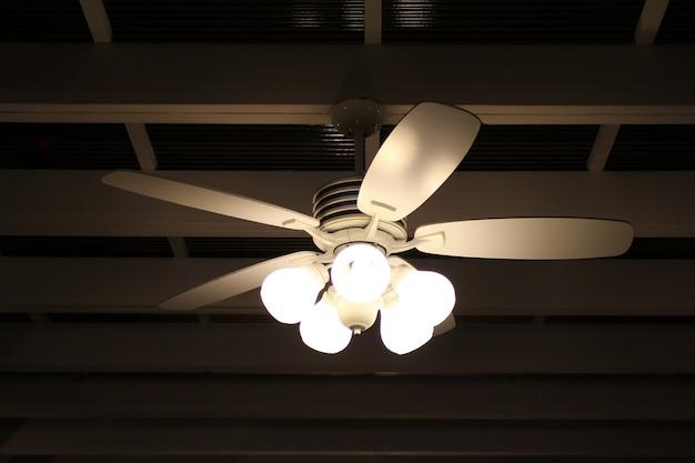 黒い背景に天井のファンとランプ