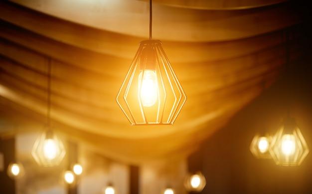 湾曲した木製の天井の下に鉄筋で作られた天井ランプ。高品質の写真