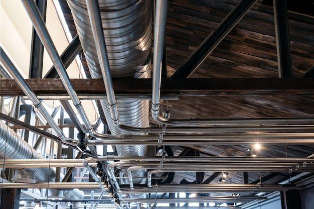 Конструкция потолка со стальными вентиляционными трубами и системами блестящих труб.