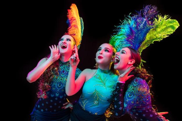Празднуйте. красивые молодые женщины в карнавале, стильный маскарадный костюм с перьями на черном фоне в неоновом свете. copyspace для рекламы. праздники, танцы, мода. праздничное время, вечеринка.
